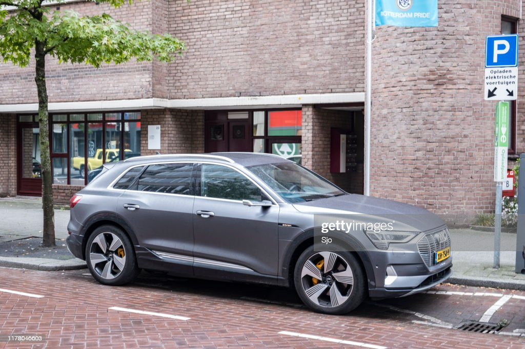 Audi e-tron 55 quattro electric SUV at an electric vehicle charging station in the city : Stock Photo