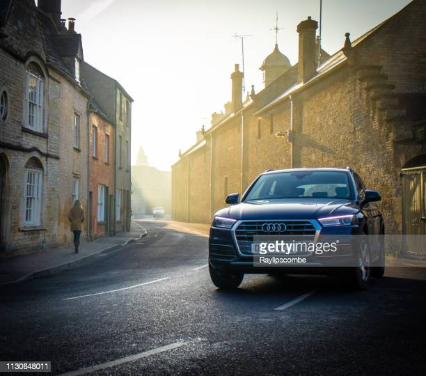 audi q7 4x4 car diving through the cotswold town of cirencester on a misty morning commute - status car stock pictures, royalty-free photos & images