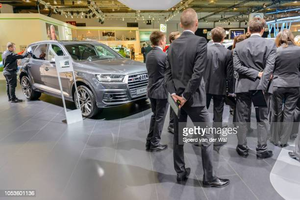 Audi Q7 SQ7 TDI luxury SUV car being polished by a man while sales persons are receiveing instructions at Brussels Expo on January 13, 2017 in...