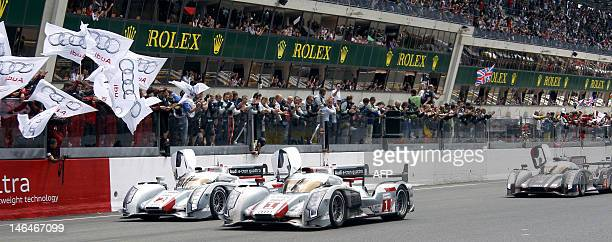 Audi R18 ETron Quattro N°1 driven by German Andre Lotterer crossing the finish line first Audi R18 ETron Quattro N°2 driven by Danish Tom Kristensen...