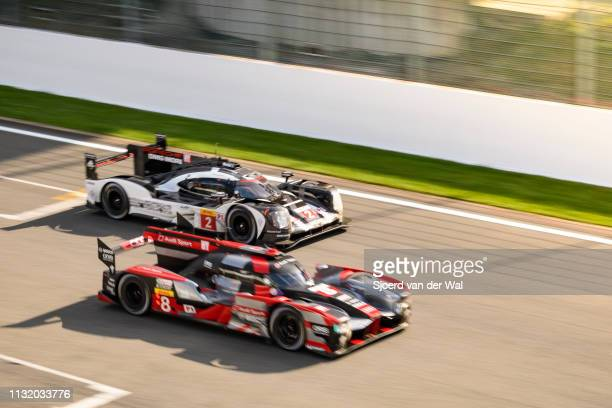 Audi Sport Team Joest R18 e-tron quattro Le Mans Prototype race car driven by Lucas di Grassi, Loïc Duval and Oliver Jarvis overtaking the Porsche...