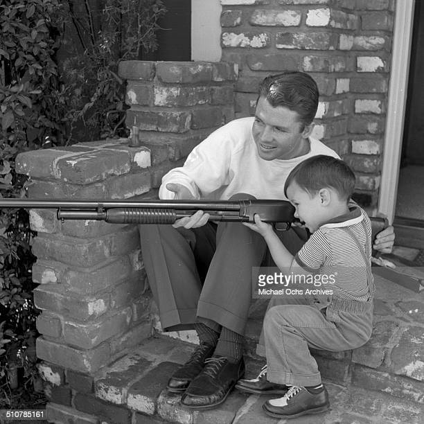Audie Murphy show his young son Terry how to hold a rifle in PerrisCA