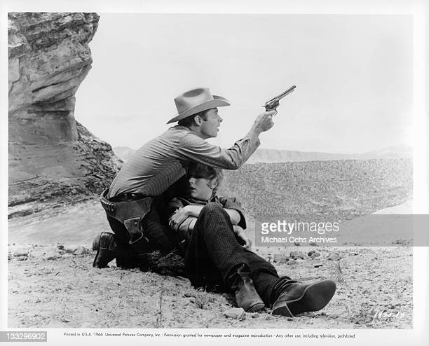 Audie Murphy takes aim at an outlaw after rescuing Joan Staley in a scene from the film 'Gunpoint' 1966