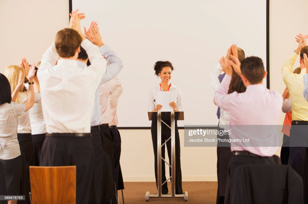 Audience applauding businesswoman at podium : Stock Photo