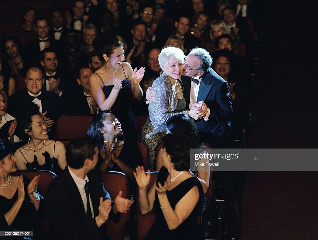 Audiencia ovacionar mujer madura, marido besar mejilla : Foto de stock