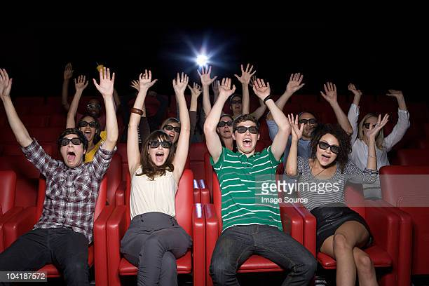 Audience at 3d movie with arms up