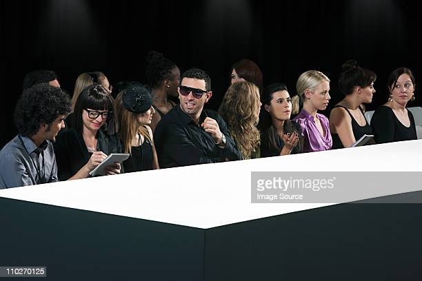 Audience at fashion show watching empty catwalk