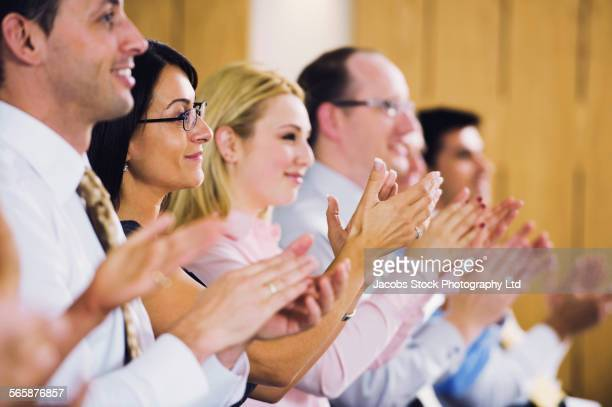 Audience clapping in applause in presentation