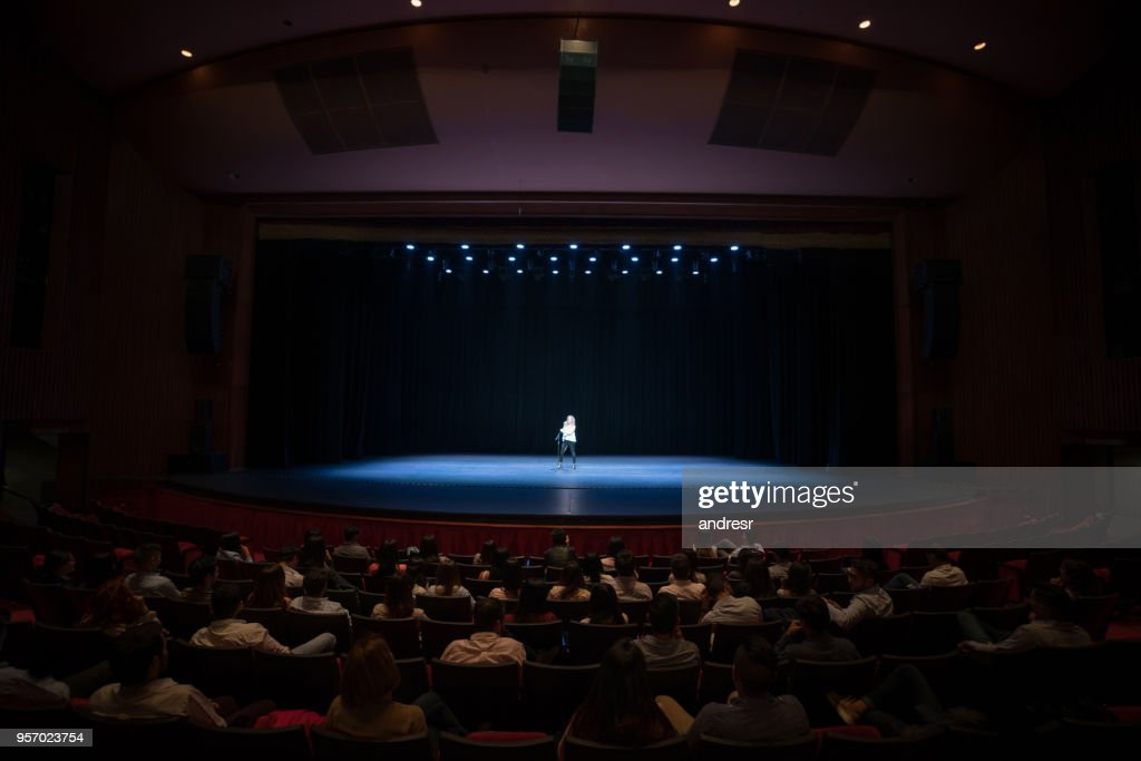 Audience enjoying a singing performance on stage : Stock Photo