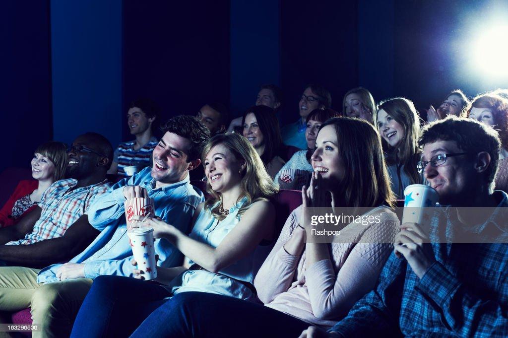 Audience enjoying movie at the cinema : Stock Photo