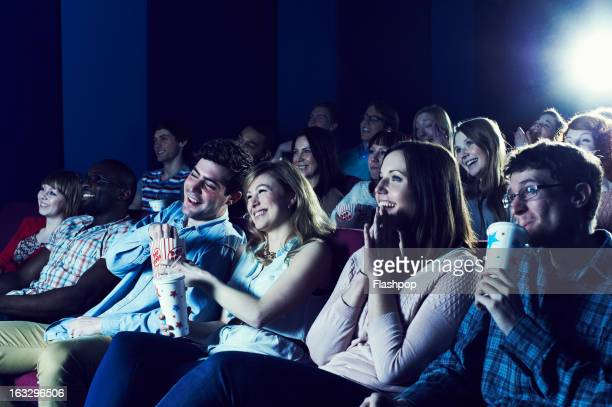 audience enjoying movie at the cinema - industria cinematografica foto e immagini stock