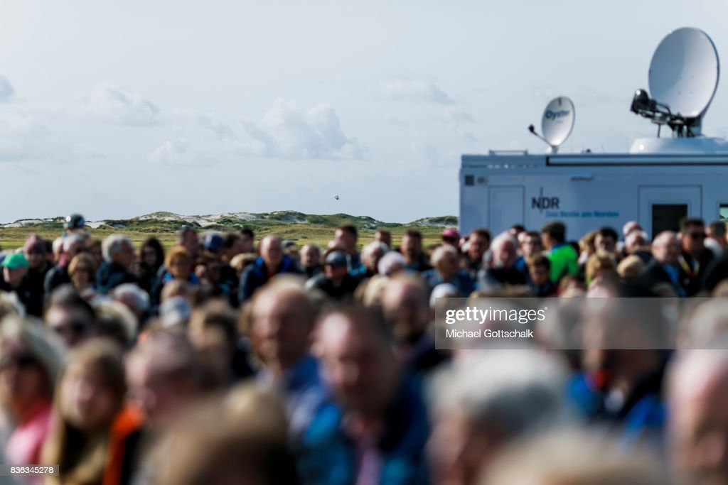 Audience in front of the dunes next to the seashore during Angela Merkels election campaign for Bundestagswahl 2017 or Federal election 2017 on August 21, 2017 in Sankt Peter-Ording, Germany.