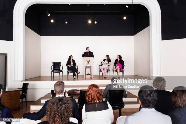 Audience listening to debate team speaking on stage