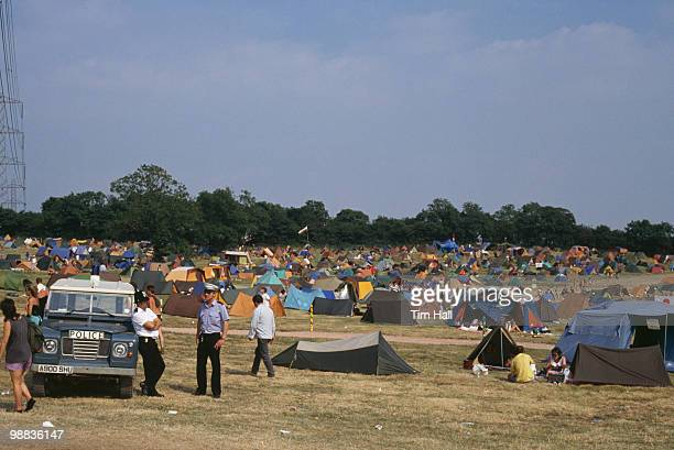 Audience members and tents and policemen at the Glastonbury Festival in June 1989