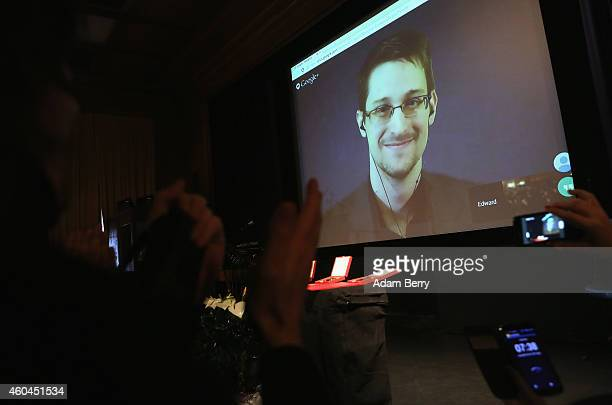 Audience members applaud as former National Security Agency contractor turned whistleblower Edward Snowden is seen on a video conference screen...