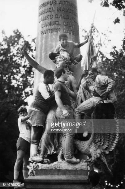 Audience members climb the Crispus Attucks Monument on Boston Common to get a better view of a concert performance by Whitney Houston in Boston on...