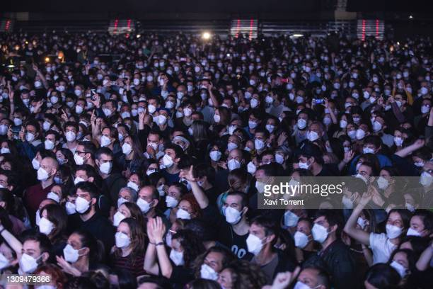 Audience members dance and wear face masks during the Love of Lesbian's concert at Palau Sant Jordi on March 27, 2021 in Barcelona, Spain. The...