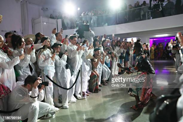 Audience members dressed in white jumpsuits watch a performer at the Desigual X Carlota Guerrero Show during Art Basel Miami 2019 at The Temple House...