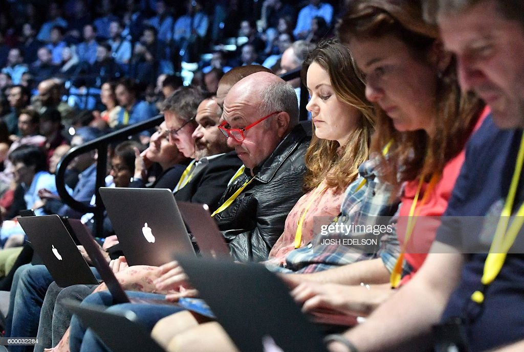 Audience members engage with their devices while Apple CEO Tim Cook speaks on stage during a media event at Bill Graham Civic Auditorium in San Francisco, California on September 07, 2016 / AFP / Josh Edelson