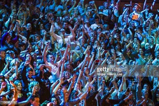Audience members enjoy the Robbie Williams performs on the second night of his tour at 02 Arena on November 23 2012 in London England