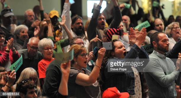 Audience members holds signs showing their displeasure with US Sen Joni Ernst at a Town Hall meeting on the campus of Drake University March 17 2017...