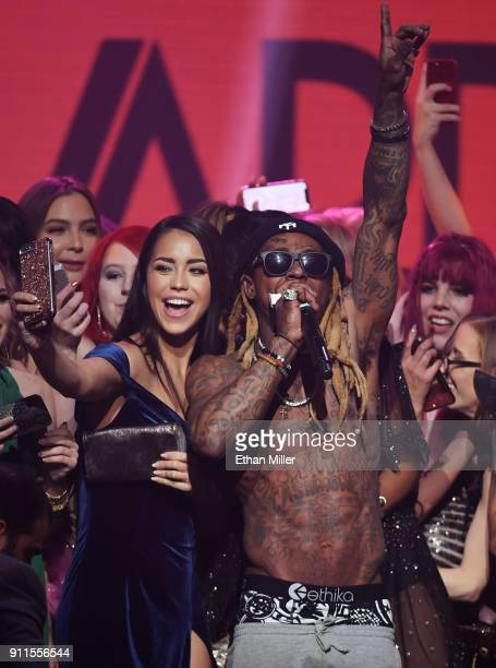 Audience members including adult film actress Alina Lopez join rapper Lil' Wayne onstage as he performs during the 2018 Adult Video News Awards at...