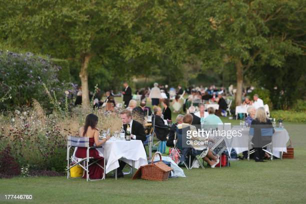 Audience members picnic in the grounds of Glyndebourne opera house in the long interval during a production of the Benjamin Britten opera 'Billy...