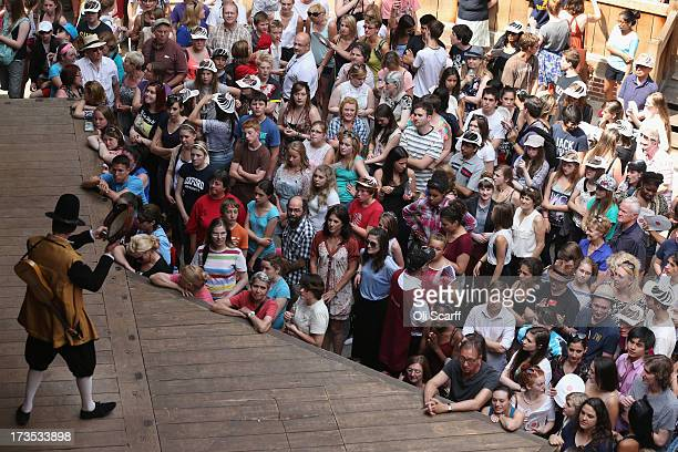 Audience members prepare to watch a production of 'A Midsummer Night's Dream' in Shakespeare's Globe theatre on the Southbank of the River Thames on...