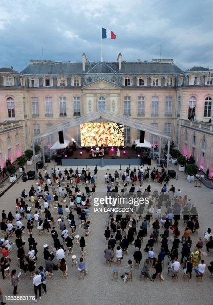 Audience members sit socially distanced in the courtyard of the Elysee Palace as they listen to electronic music performer Irene Dresel during...