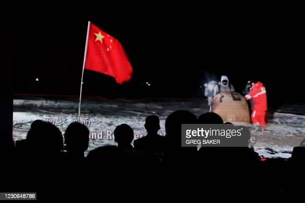Audience members take photos of a screen showing a video about China's Chang'e-5 moon probe at an event announcing details of international access to...