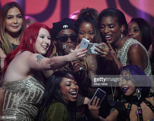 Audience members take selfies with rapper Lil' Wayne onstage as he performs during the 2018 Adult Video News Awards at The Joint inside the Hard Rock...