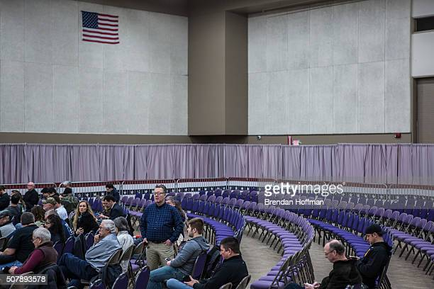 Audience members wait for the start of a campaign rally with Republican presidential candidate Donald Trump at the Ramada Waterloo Hotel and...