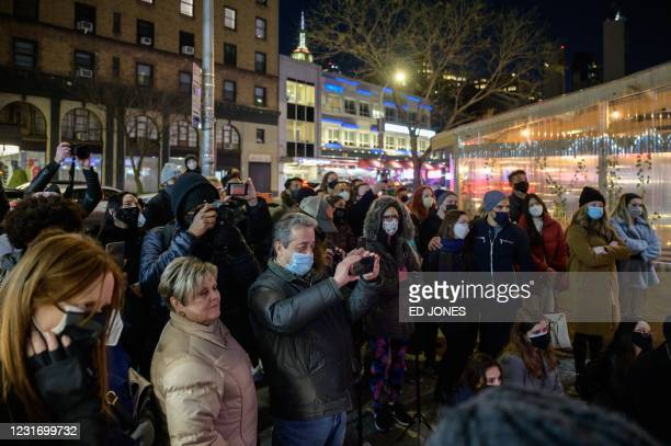 Audience members watch as performers stage a free production of Romeo and Juliet in a vacant shop window on a west side street in Manhattan, New...