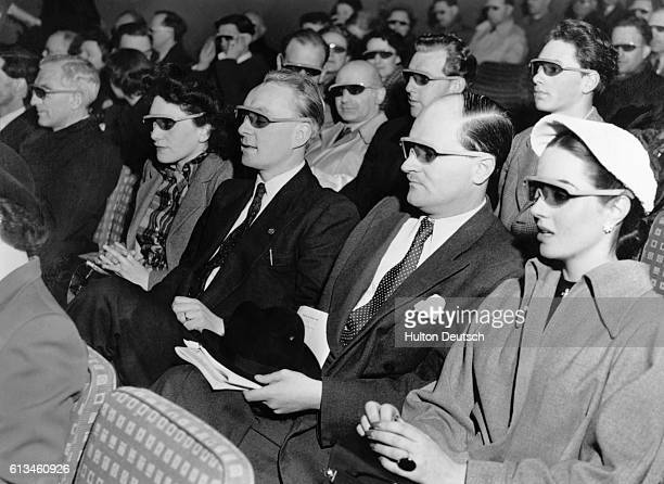 Audience members watching a threedimensional movie are wearing the '3D' goggles required to see such movies properly Ca 1950s
