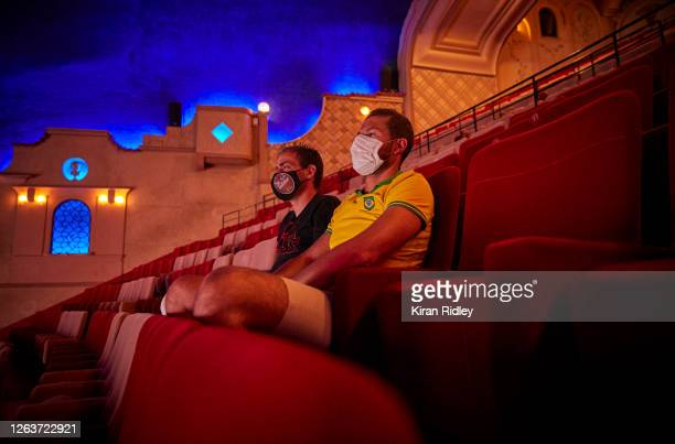 Audience members wearing masks watch one of the last screenings in the Grand Salle, the largest auditorium in Europe, at the Grand Rex cinema before...