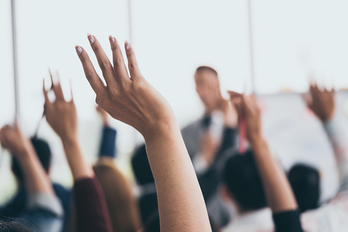Audience raising hands up while businessman is speaking in training at the office. 1041740040