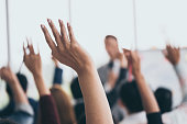 Audience raising hands up while businessman is speaking in training at the office.