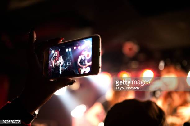 audience shooting with smartphone while enjoying live performances - 芸能イベント ストックフォトと画像