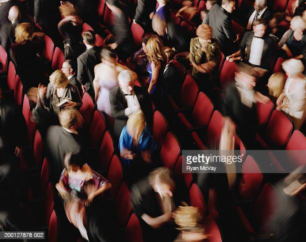 Audience standing in rows of  theater seats, overhead view