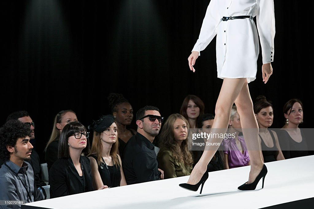 Audience watching model on catwalk at fashion show, low section : Stock Photo