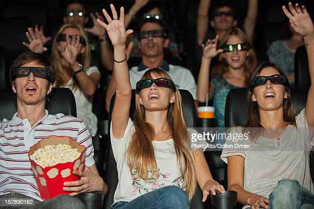 Audience wearing 3-D glasses in movie theater, arms reaching out