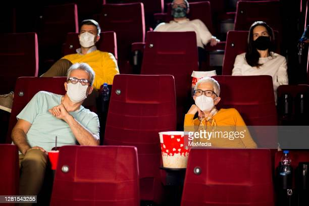 audience wearing face masks while watching a movie at the cinema - film premiere stock pictures, royalty-free photos & images
