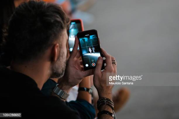Audience with cell phones recording and live with facebook live instagram igtv and snapchat at Sao Paulo Fashion Week N46 SPFW Winter 2019 at ARCA on...