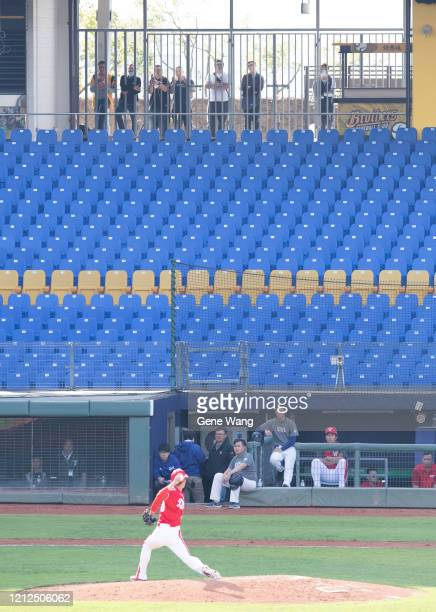 Audiences watch the closed door game through the fence during the CPBL preseason game between CTBC Brothers and Wei Chuan Dragons at the Taichung...
