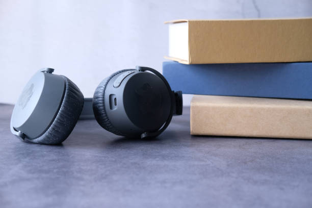 Audio Book Concept. Headphones And Book Over Wooden Table