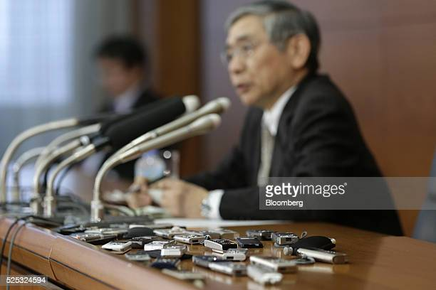 Audio recorders are placed near Haruhiko Kuroda governor of the Bank of Japan as he speaks during a news conference at the central bank's...