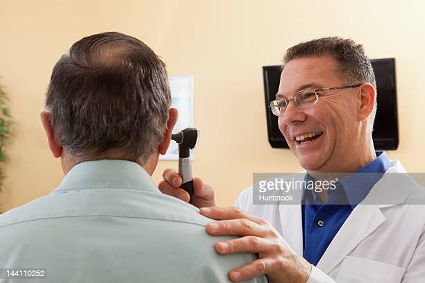 audiologist doing an ear canal inspection of a patient - ear canal stock photos and pictures