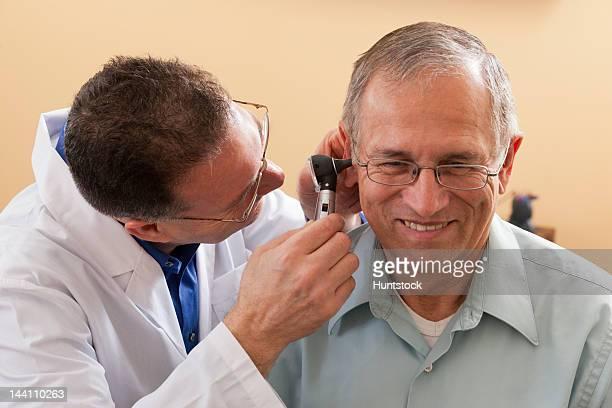 audiologist doing an ear canal inspection - ear canal stock-fotos und bilder