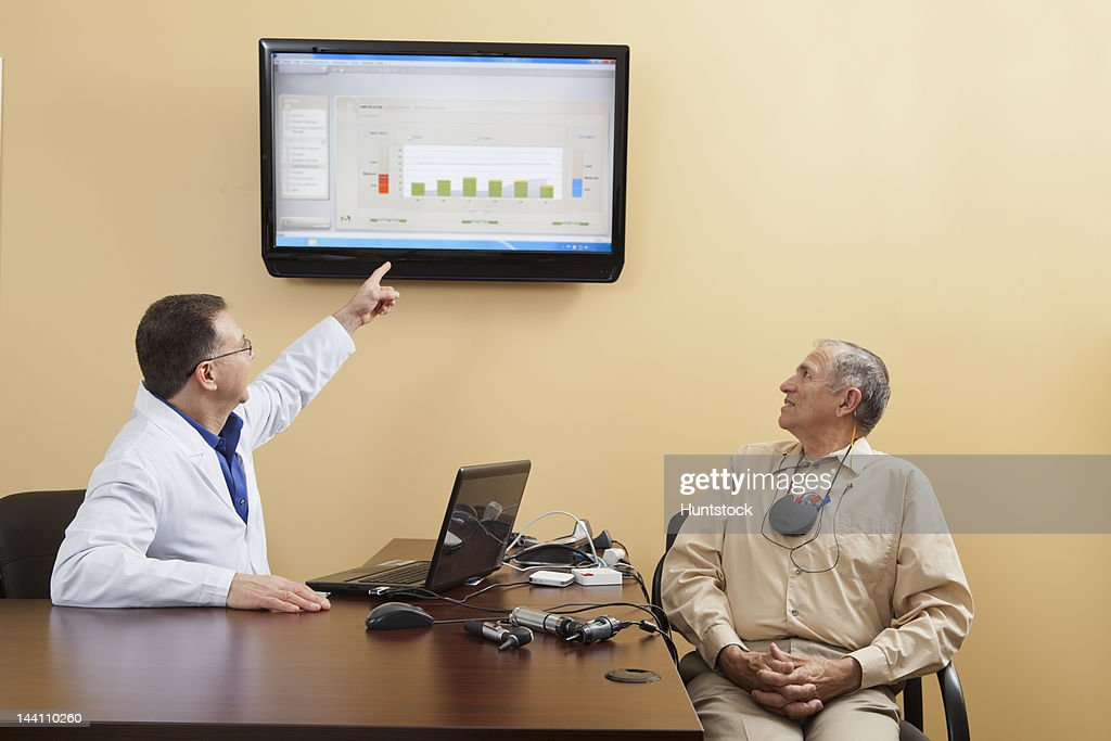 Audiologist explaining diagrams for a patient wearing hearing device programmer : Stock Photo