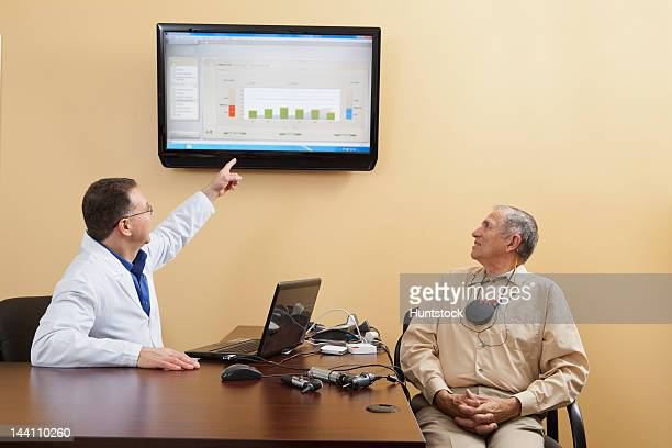 audiologist explaining diagrams for a patient wearing hearing device programmer - ear canal stock-fotos und bilder
